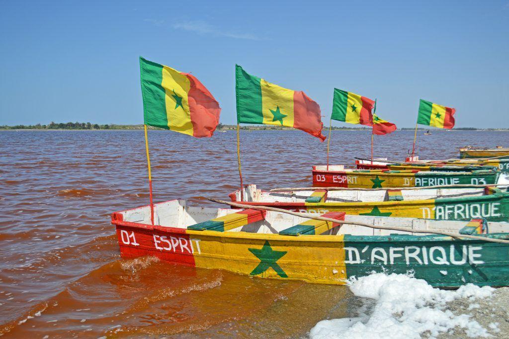 Barcas con la bandera de Senegal en el lago rosado o lago retba cercano a Dakar